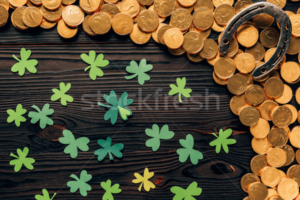 top view of shamrock, golden coins and horseshoe on wooden table, st patricks day concept Stock photo © LightFieldStudios