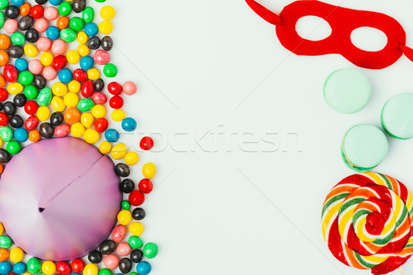 top view of arranged party cone, masquerade mask, macarons and candies isolated on grey Stock photo © LightFieldStudios