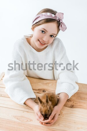 beautiful girl looking at camera while sitting with furry rabbits and basket with easter eggs in nes Stock photo © LightFieldStudios