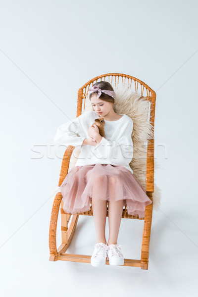 beautiful girl holding furry rabbit while sitting on rocking chair isolated on white  Stock photo © LightFieldStudios