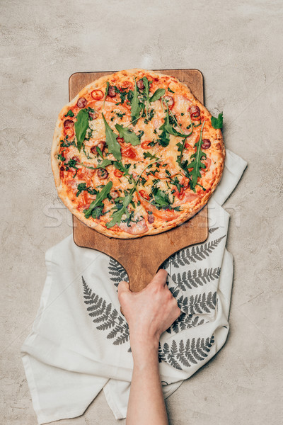 Close-up view of hand holding pizza on wooden cutting board on light background Stock photo © LightFieldStudios