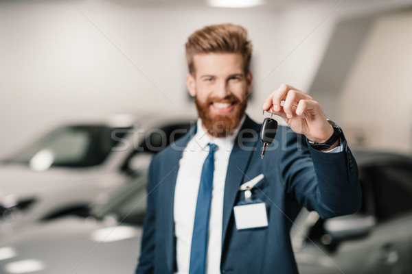 salesman in suit holding car key and looking at camera in dealership salon   Stock photo © LightFieldStudios