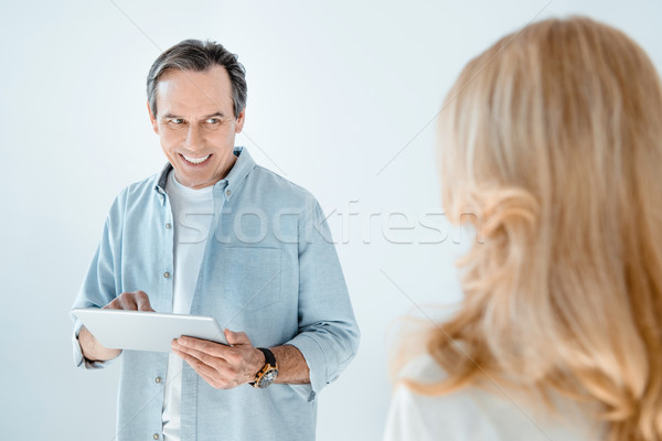 Happy mature man with digital tablet looking at blonde woman on grey Stock photo © LightFieldStudios