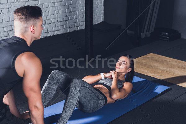 woman doing abs exercises with trainer Stock photo © LightFieldStudios