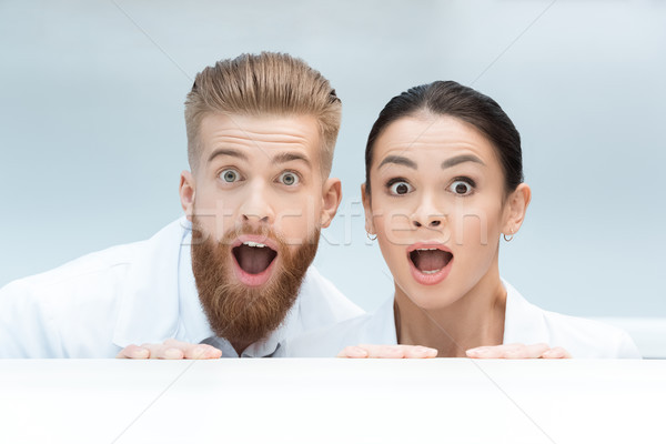 portrait of shocked scientists looking out behind table in lab Stock photo © LightFieldStudios