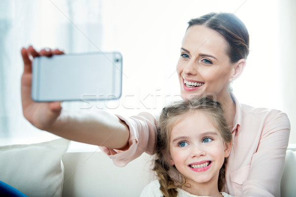 portrait of cheerful daughter and mother making selfie together Stock photo © LightFieldStudios