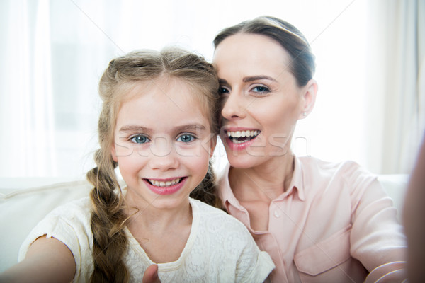 camera point of view of smiling mother and daughter making selfie Stock photo © LightFieldStudios