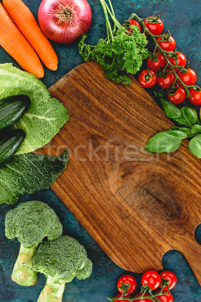 top view of fresh healthy raw vegetables and wooden cutting board Stock photo © LightFieldStudios