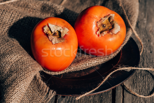 two delicious persimmons on sackcloth on wooden table Stock photo © LightFieldStudios