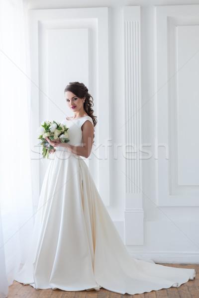 smiling bride posing in elegant dress with wedding bouquet Stock photo © LightFieldStudios