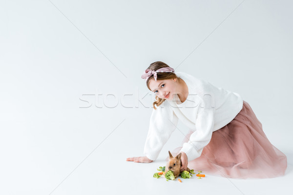 beautiful girl smiling at camera while feeding bunny isolated on white  Stock photo © LightFieldStudios