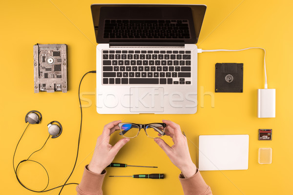 cropped shot of person holding eyeglasses while fixing laptop on yellow Stock photo © LightFieldStudios