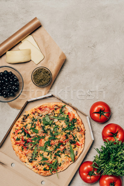 Whole pizza in cardboard box with tomatoes, cheese and olives on light background Stock photo © LightFieldStudios