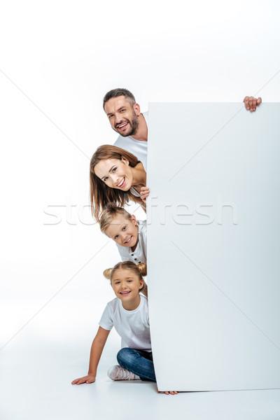 Smiling family holding blank card Stock photo © LightFieldStudios