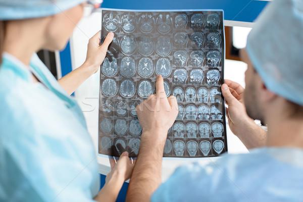 surgeons in medical uniforms examining x-ray image on white Stock photo © LightFieldStudios