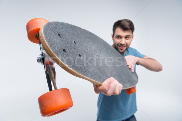 man holding skateboard in hands on white Stock photo © LightFieldStudios