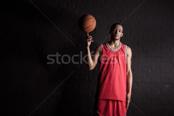 african sporty man holding basketball ball on finger on black Stock photo © LightFieldStudios