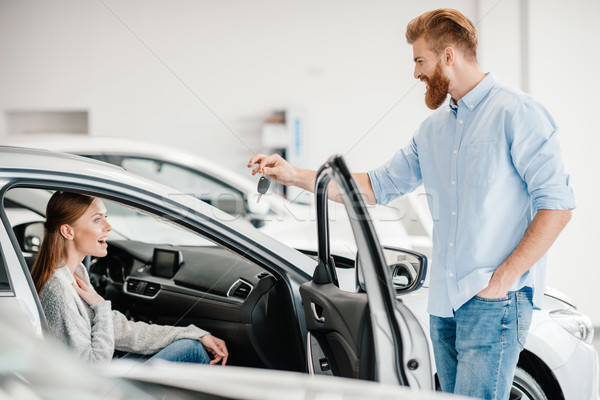 Man giving car key to woman sitting in car in dealership salon    Stock photo © LightFieldStudios