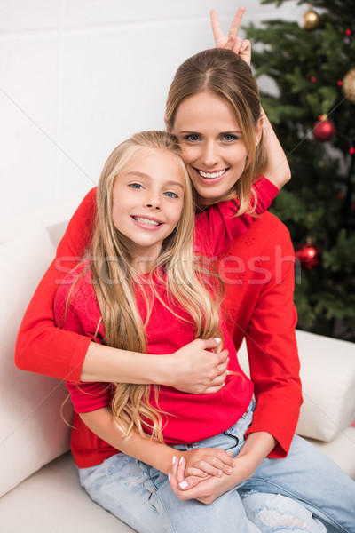 mother and daughter embracing at christmas tree Stock photo © LightFieldStudios