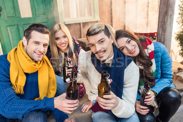 Stock photo: happy friends with beer spending time together and looking to camera