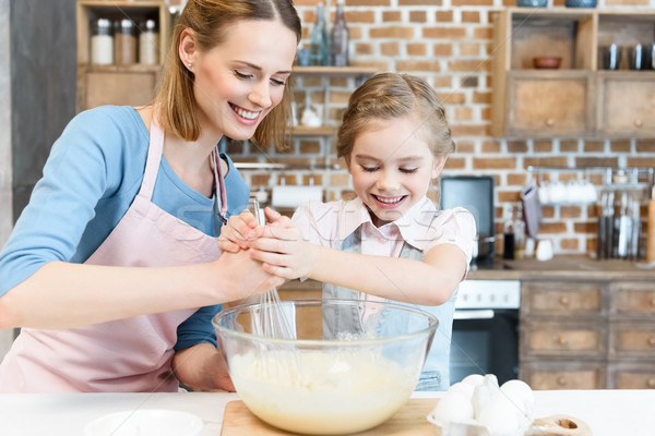 Happy mother and daughter mixing dough in glass bowl  Stock photo © LightFieldStudios