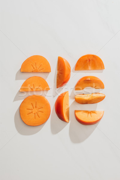 top view of persimmons pieces in rows on white tabletop Stock photo © LightFieldStudios