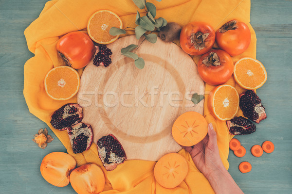cropped image of woman holding piece of persimmon Stock photo © LightFieldStudios