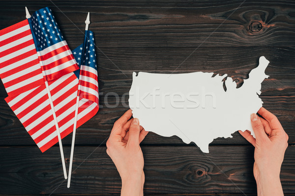 top view of arranged american flags and female hands with piece of blank map on wooden tabletop, pre Stock photo © LightFieldStudios