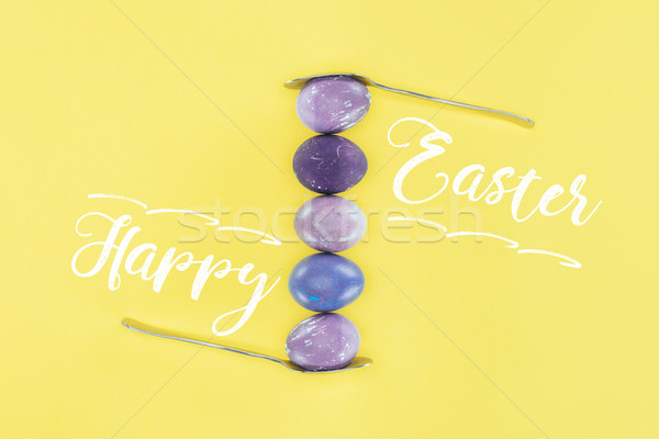 top view of shabby painted eggs between two spoons, isolated on yellow with Happy Easter lettering Stock photo © LightFieldStudios