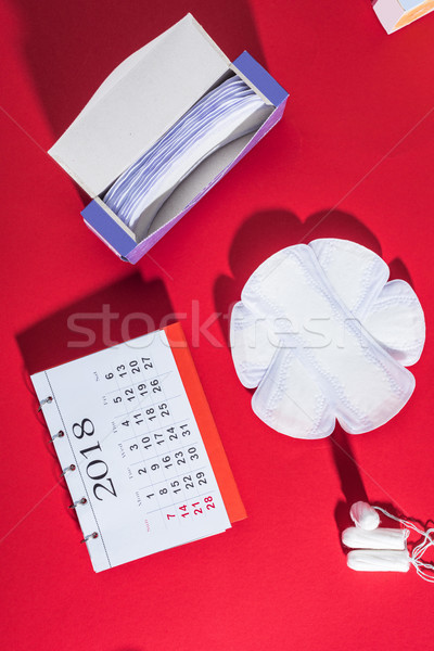 top view of menstrual tampons, daily liners and calendar on red Stock photo © LightFieldStudios