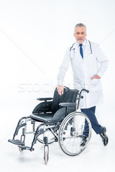 Smiling doctor with wheelchair  Stock photo © LightFieldStudios