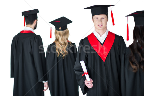 young student in graduation cap with diploma, with friends behind isolated on white Stock photo © LightFieldStudios