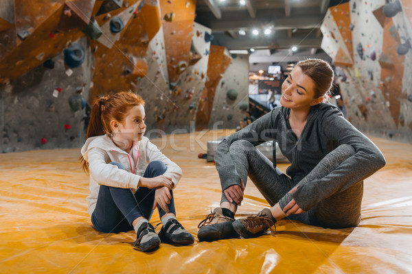 Stock photo: Girl and mom sitting on mat at gym