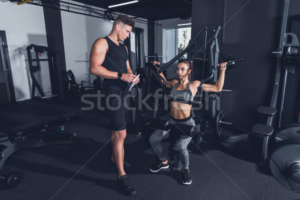 trainer and sportive woman in gym Stock photo © LightFieldStudios