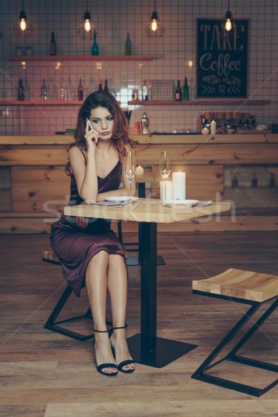 woman talking on smartphone in restaurant Stock photo © LightFieldStudios