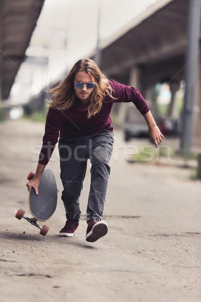 Hombre equitación skateboard guapo joven puente Foto stock © LightFieldStudios