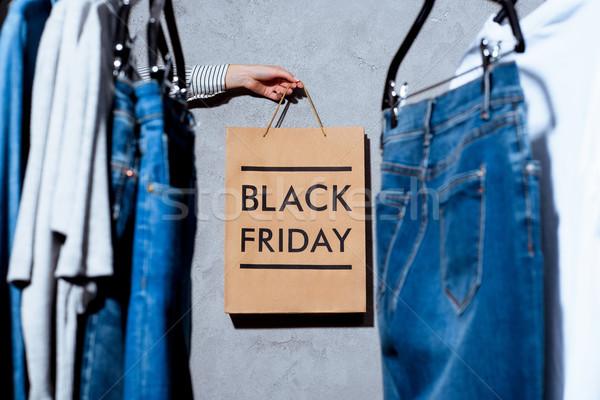 hand with shopping bag on black friday Stock photo © LightFieldStudios