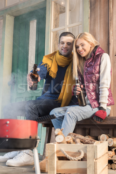 Happy young couple drinking beer and looking at grill on porch Stock photo © LightFieldStudios
