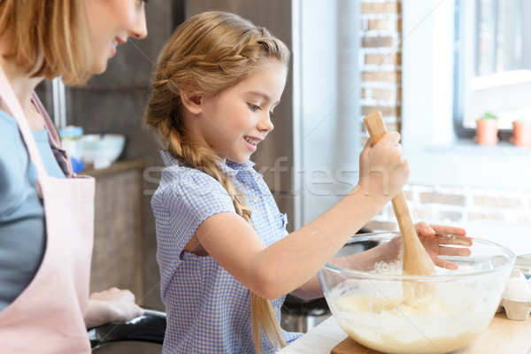 Happy mother looking at little daughter preparing dough in glass bowl Stock photo © LightFieldStudios