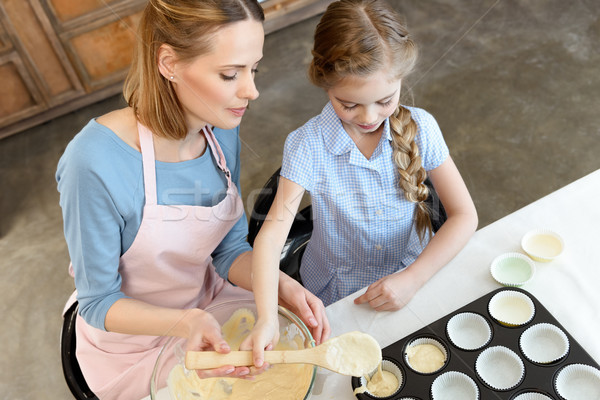 High angle view of mother and daughter cooking with dough and baking form Stock photo © LightFieldStudios