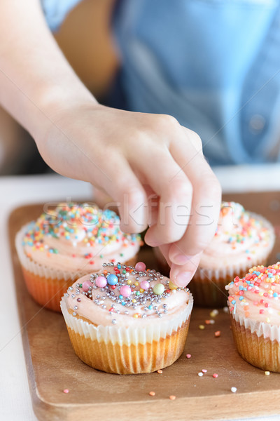close up view of girl's hand decorating cupcakes with confetti Stock photo © LightFieldStudios