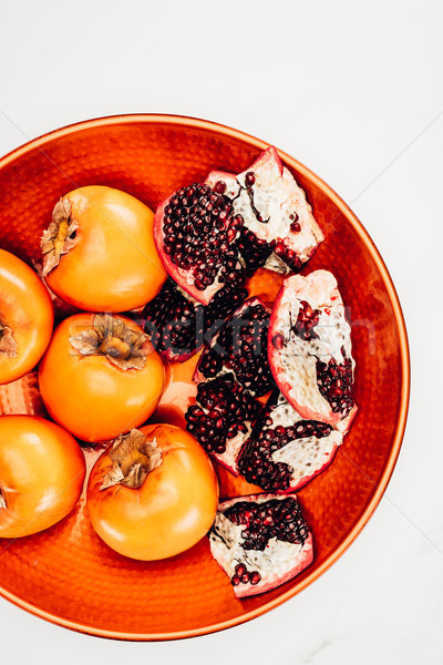 elevated view of persimmons and pomegranates on red plate isolated on white Stock photo © LightFieldStudios