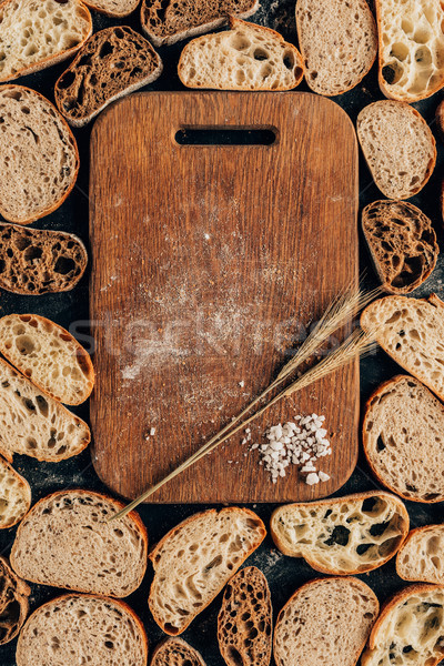 top view of arranged pieces of bread and wooden cutting board with wheat and salt Stock photo © LightFieldStudios