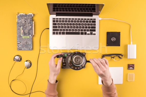 cropped shot of person holding magnifying glass while repairing laptop Stock photo © LightFieldStudios