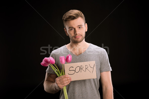 portrait of man looking to camera while holding tulips bouquet and sorry sign on black Stock photo © LightFieldStudios