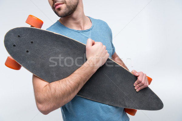 partial view of man holding skateboard in hands on white Stock photo © LightFieldStudios