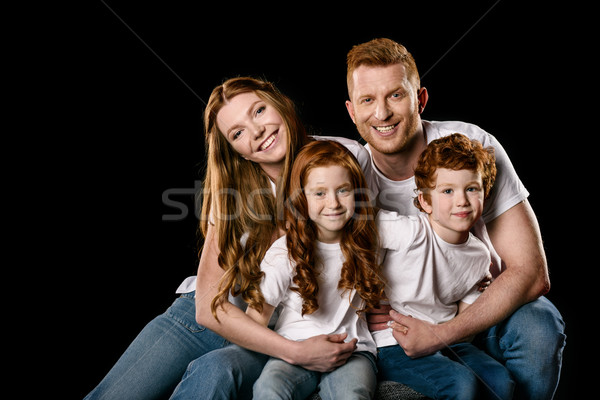 Happy redhead family sitting embracing and smiling at camera isolated on black  Stock photo © LightFieldStudios
