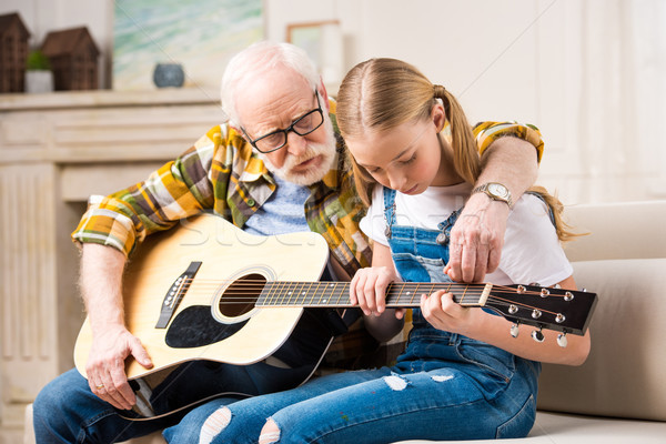 Concentrated girl with senior man sitting on sofa and playing acoustic guitar Stock photo © LightFieldStudios