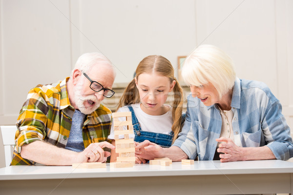 Emotional senior couple with granddaughter playing jenga game at home Stock photo © LightFieldStudios