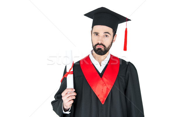 Frowning bearded young student holding diploma and looking at camera Stock photo © LightFieldStudios